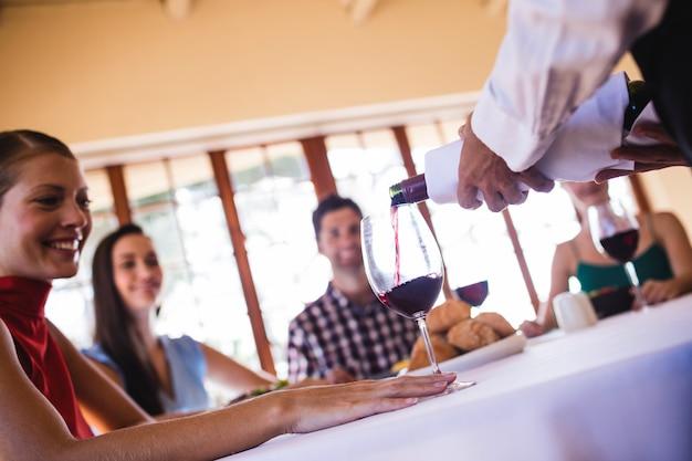 Serveerster die rode wijn in wijnglas gieten op lijst