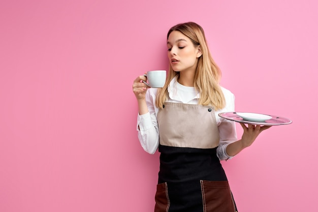 Serveerster die van hete koffie geniet die over roze studioachtergrond wordt geïsoleerd