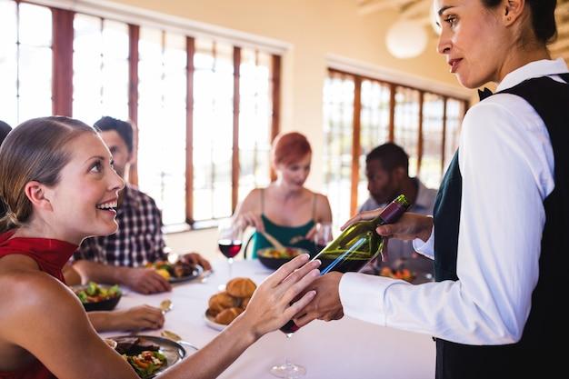 Serveerster die wijn tonen aan klant bij lijst