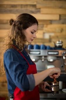 Serveerster gebruikt een stamper om gemalen koffie in een filterhouder te drukken
