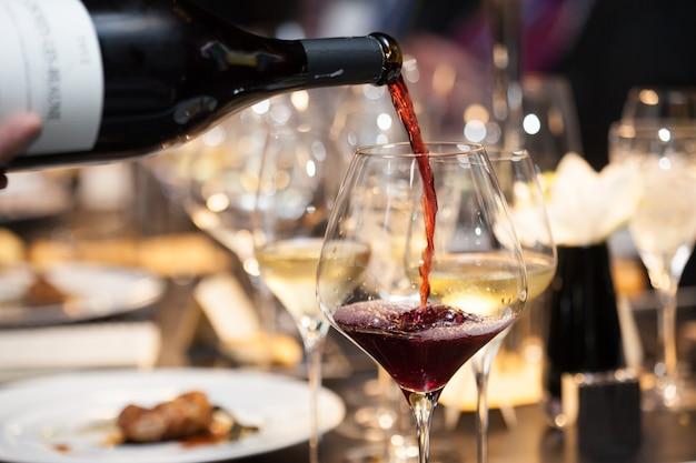 Serveerster giet rode wijn in het glas op tafel in restaurant