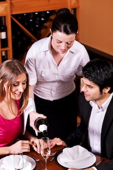 Serveerster glazen vullen met champagne