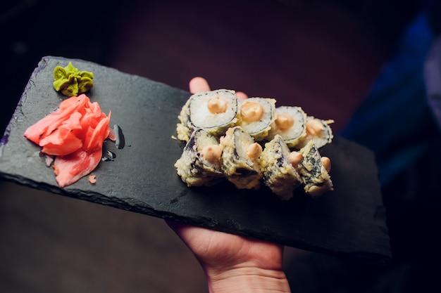 Serveerster in sushi restaurant met sushi plaat