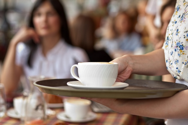 Serveerster met dienblad met kopjes koffie in cafetaria