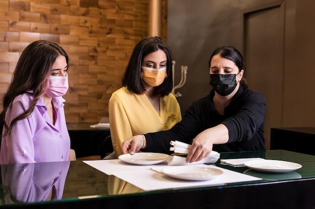 Serveerster met gezichtsmasker en sociale afstand tot een spaanse vrouwelijke klant professioneel sushi-restaurantpersoneel in het nieuwe normale leven met covid19 pandemie gele kleur 2021 jaar
