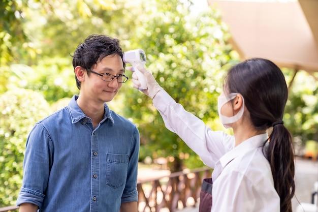 Serveerster met gezichtsmasker neemt temperatuur naar klanten