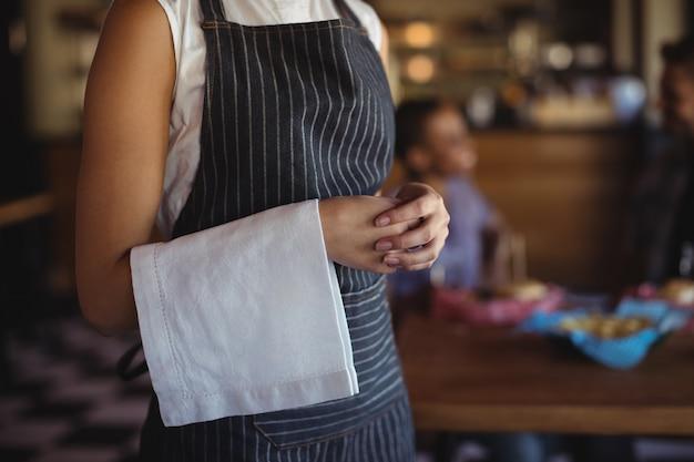 Serveerster met servet dat zich bij restaurant bevindt