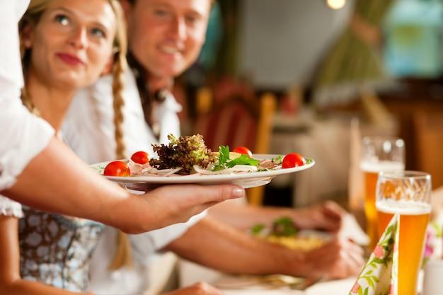 Serveerster serveert een beiers restaurant