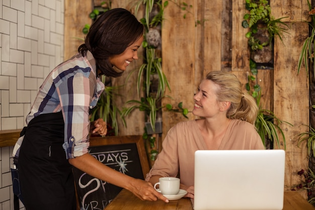 Serveerster serveert een kopje koffie aan de klant