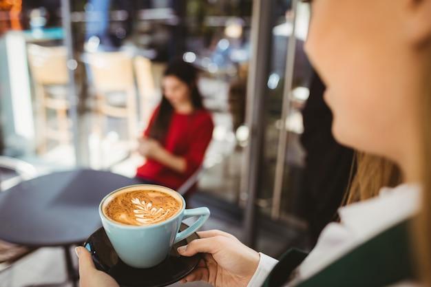 Serveerster serveert een kopje koffie in het café