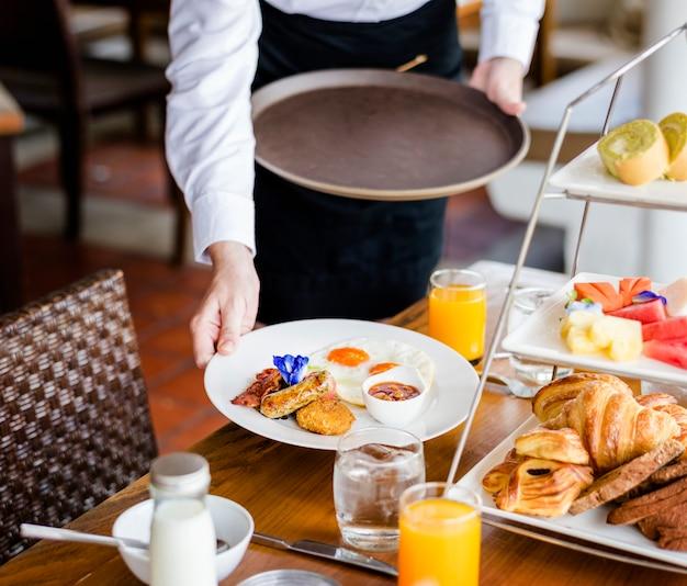 Serveerster serveert ontbijt in een restaurant