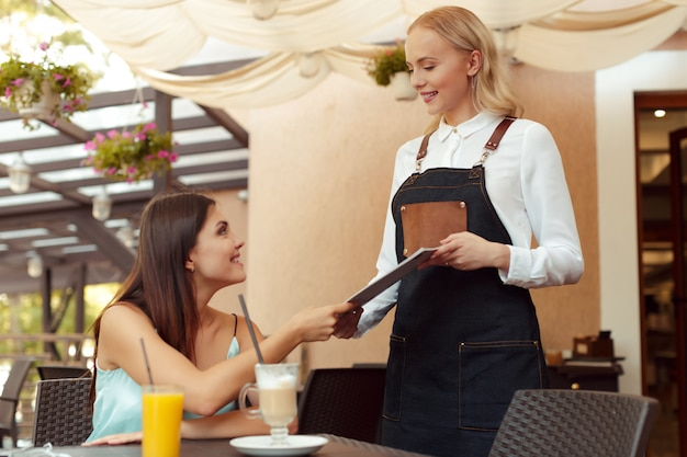 Serveerster server helpt client in café