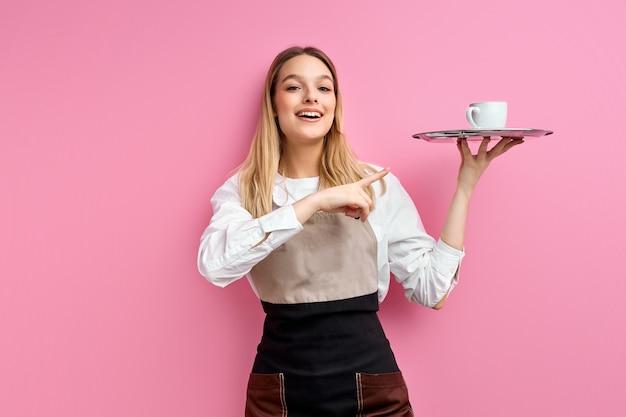 Serveerster vrouw in schort met dienblad met kopje koffie, kijkend met verrast gezicht wijzende vinger naar beker