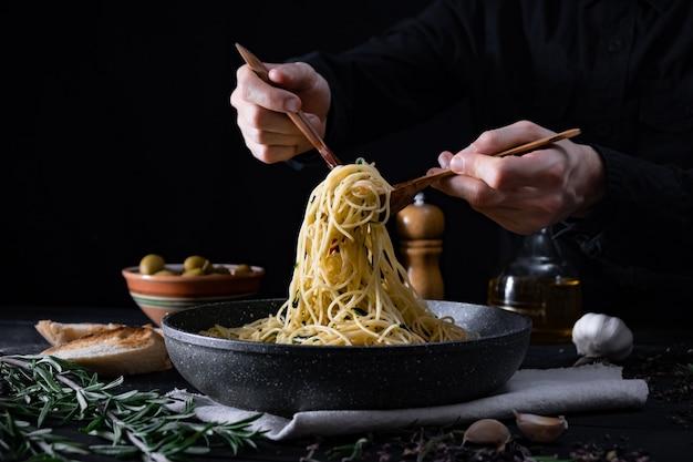 Serveert traditionele italiaanse pasta uit een pan. mannelijke handen die spaghetti in lepel en vork nemen, schot in rustig