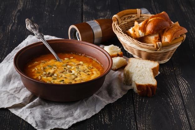 Serveren op rustieke tafel, traditionele kruiden pompoensoep in kom