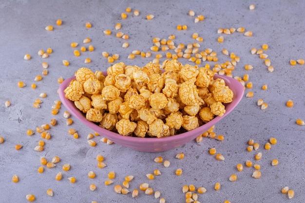 Serveren van karamelpopcorn met maïskorrels verspreid over marmeren achtergrond. hoge kwaliteit foto