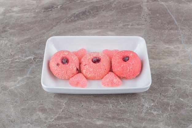Serveren van koekjes en gelei-snoepjes op een schaal op een marmeren oppervlak