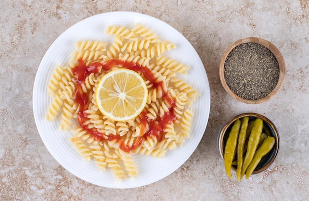 Serveren van macaroni met kleine kommen zwarte peper en ingemaakte pepers op marmeren oppervlak.