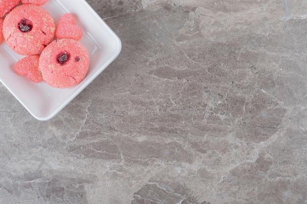 Serveren van roze koekjes en gelei-snoepjes op een schaal op een marmeren oppervlak