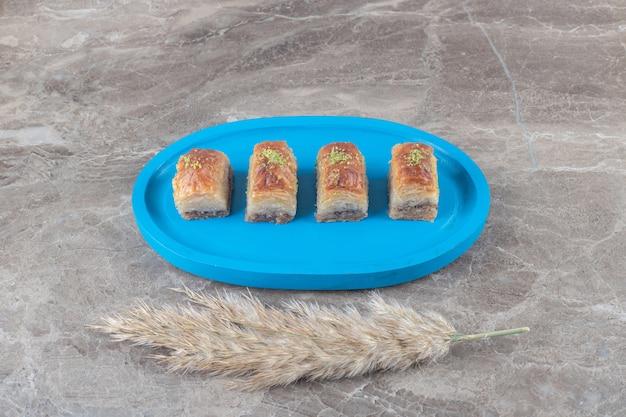 Serveren van turkse bakhlava's en verengrasstengels op marmeren ondergrond