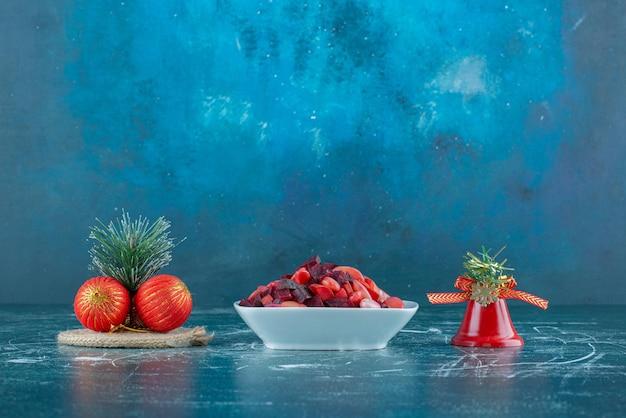 Serveren van vinegret salade en bundel kerstballen op blauw.