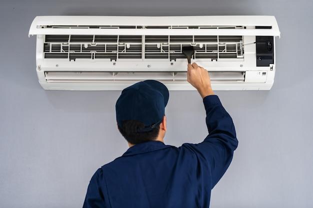 Service door technicus met borstel om de airconditioner te reinigen