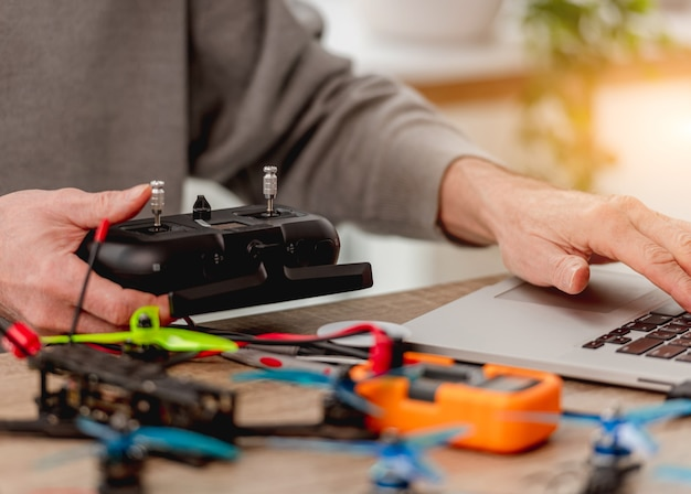 Service man zit bij de tafel met reparatie tools, laptop gebruikt en quadcopter bedieningspaneel in zijn handen te houden