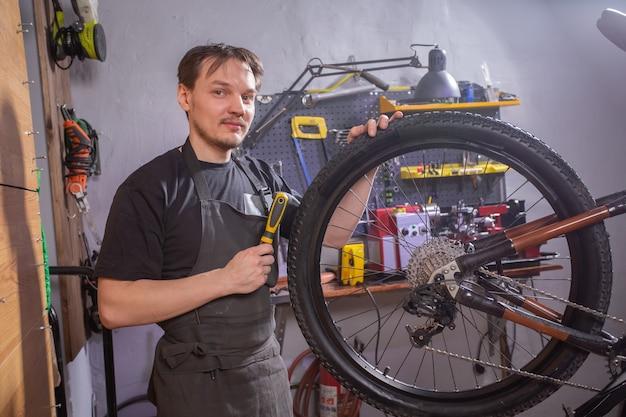 Service, reparatie, fiets en mensen concept - monteur repareren van een mountainbike in een werkplaats