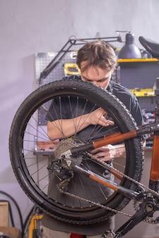Service-, reparatie-, fiets- en mensenconcept - monteur die een mountainbike in een werkplaats herstelt