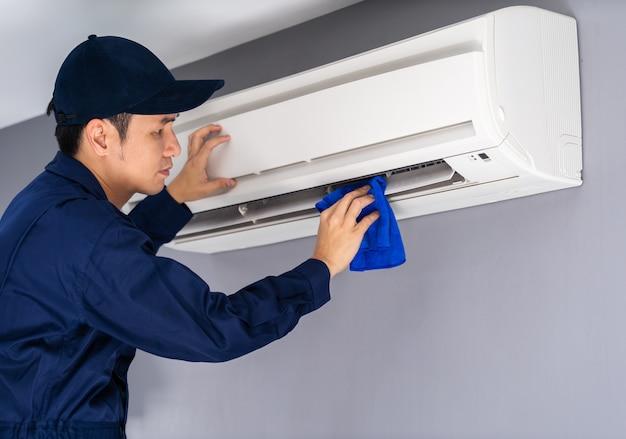 Service van de technicus reiniging airconditioner met doek