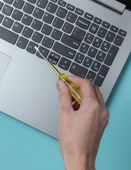 Servicecentrum laptop reparatie hand houdt een schroevendraaier in de buurt van een laptop