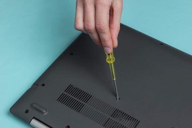 Servicecentrum laptop reparatie vrouwelijke handschroevendraaier draait laptopbout los