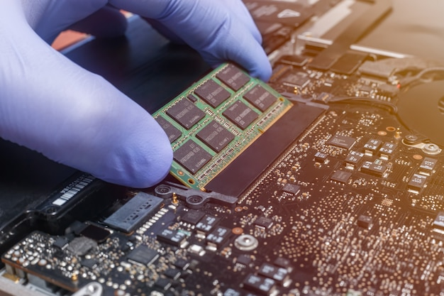 Servicemonteur installeert nieuwe ram-geheugenchips op de laptop