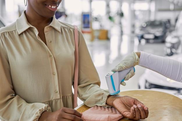 Servicepersoneel controleert de temperatuur van klanten voordat ze naar auto's kijken