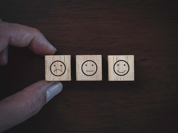 Services rating, ranking, review, feedback en klanttevredenheidsonderzoek concept. close-up vinger kiezen niet tevreden gezicht emoticon pictogram op houten kubusblok op donkere houten achtergrond, bovenaanzicht.