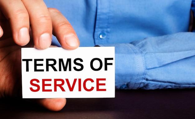 Servicevoorwaarden zijn geschreven op een wit visitekaartje in de hand van een man. reclame concept