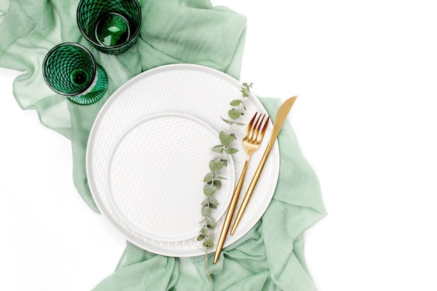 Servies en decoraties voor het serveren van een feestelijke tafel. borden, wijnglazen en bestek met grijs decoratief textiel op witte achtergrond.