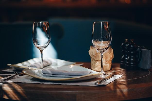Serviesglazen, bloemvork, mes geserveerd voor het diner in restaurant met gezellig interieur