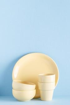 Serviesgoed en bestek op een blauwe pastel achtergrond met kopie ruimte