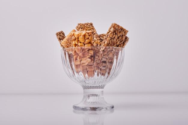 Sesam- en notencrackers in een glazen beker.