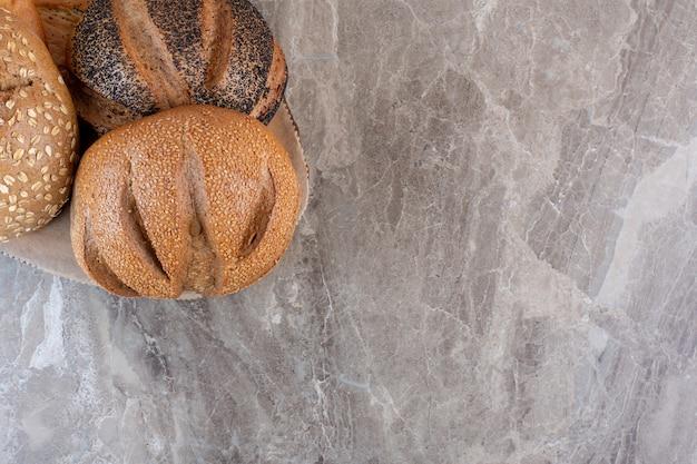 Sesam gecoate verscheidenheid van broodbroden op een houten bord op marmer.