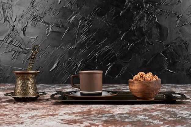 Sesamnoten en een kopje koffie op een houten bord.