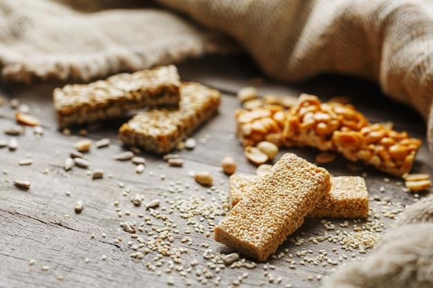 Sesamzaadcasino's met jutedoek. landelijke stijl. heerlijke zoetigheden van zaden van zonnebloem, sesam en pinda's, bedekt met glanzend glazuur