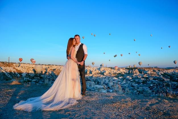 Sessie bruidspaar in cappadocië, turkije met hete lucht ballonnen