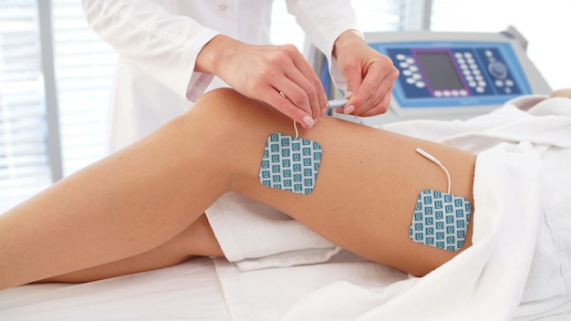 Sessie van myostimulatie op de benen van vrouwen in een cosmetologiekliniek