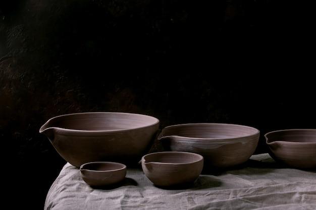 Set ambachtelijke handgemaakte ongeglazuurde donkere klei aardewerk kommen met tuit op tafel met donkere tafel.