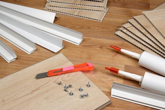 Set artikelen voor binnenwerk van pvc-plafonds. montage zelfklevende flessen en pvc panelen met kunststof hoeken. vpc-gevelbeplating voor binnenshuis. interieurrenovatiewerken of bouwmaterialen