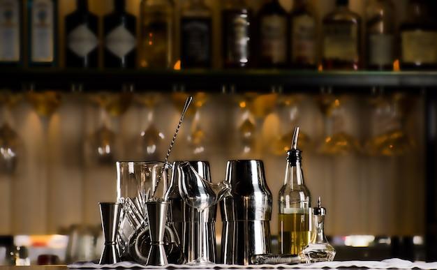 Set baraccessoires voor het maken van cocktails, gelegen aan de bar, daarachter is een plank met likeuren en sterke alcohol. gemengde media