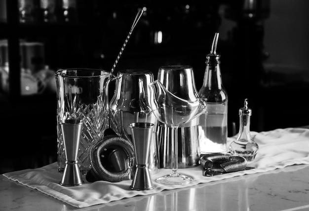 Set baraccessoires voor het maken van cocktails, gelegen op de bar, daarachter is een plank met likeuren en sterke alcohol. gemengde media