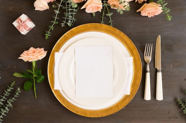 Set borden en keukengerei met bloemen op houten achtergrond